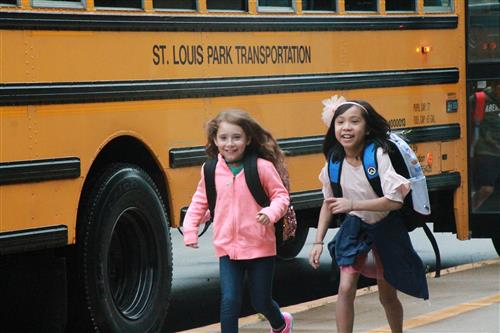 Two kids getting off of a St. Louis school bus