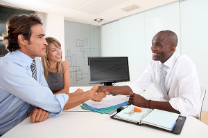 Real estate agent shaking hands with buyers