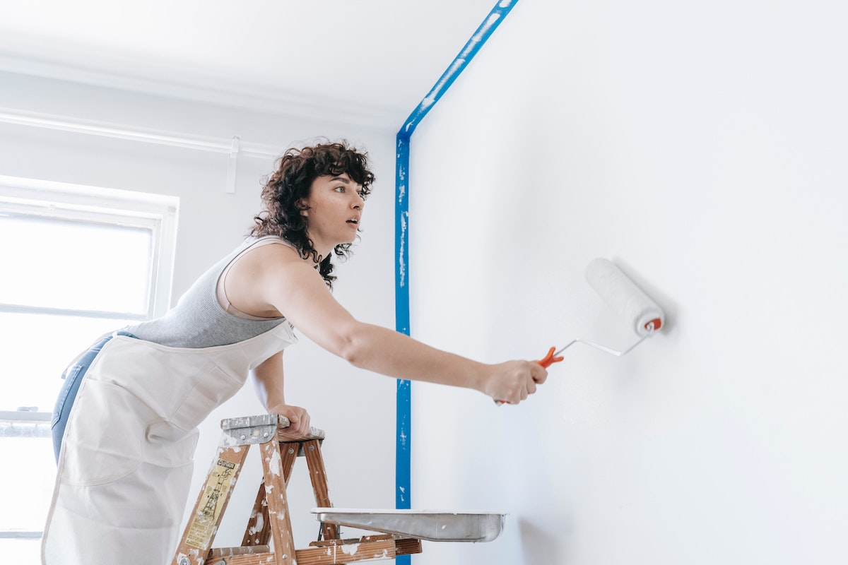 Woman painting a room before selling her house as-is
