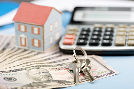 Calculator, cash and house keys, symbolizing the costs of homes for first time buyers
