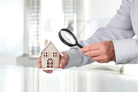 Man holding a house model under a magnifying glass, symbolizing differences in home inspector credentials in Missouri vs. Illinois
