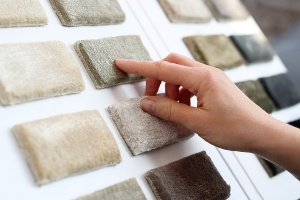hand touching carpet samples