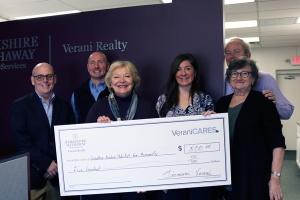 Verani agents holding big check