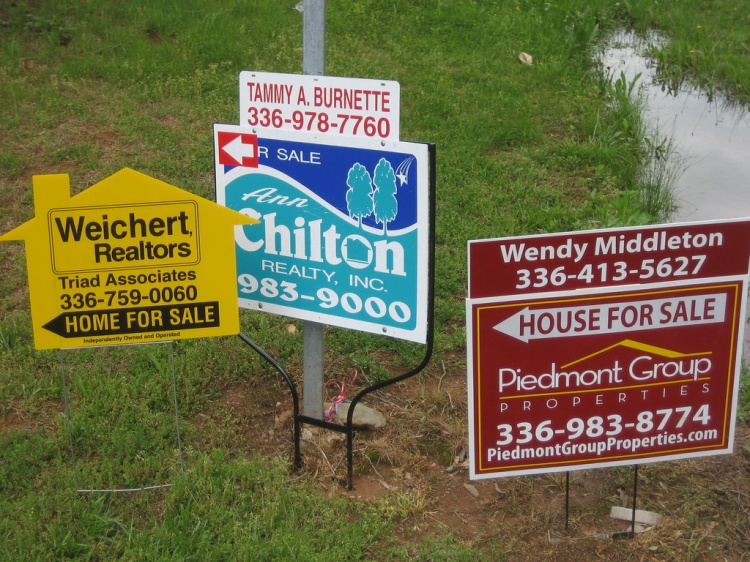 three different home for sale signs from three different realtors