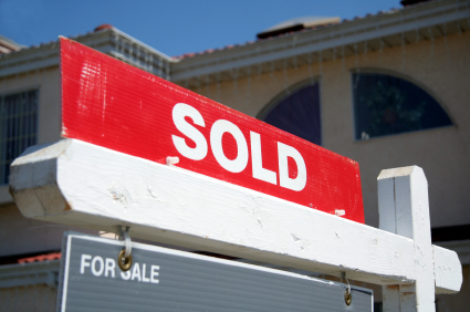 """Sold"" sign in front of a house as real estate demand remains high"